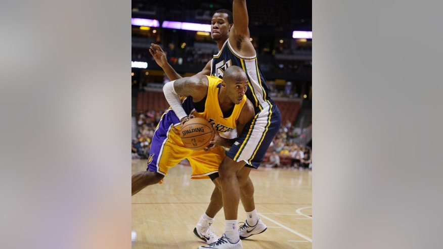 Los Angeles Lakers' Kobe Bryant, left, looks for a way around Utah Jazz's Rodney Hood during the second half of a preseason NBA basketball game Thursday, Oct. 16, 2014, in Anaheim, Calif. The Jazz won 119-86. (AP Photo/Jae C. Hong)