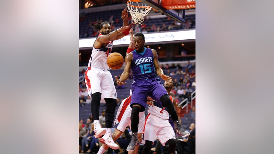 Charlotte Hornets guard Kemba Walker (15) passes the ball with Washington Wizards forward Nene, left, from Brazil, and guard John Wall, right, nearby, during the first half of a preseason NBA basketball game, Friday, Oct. 17, 2014, in Washington. (AP Photo/Alex Brandon)