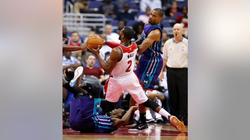 Washington Wizards guard John Wall (2) is fouled by Charlotte Hornets guard Gary Neal, right, during the first half of a preseason NBA basketball game, Friday, Oct. 17, 2014, in Washington. (AP Photo/Alex Brandon)