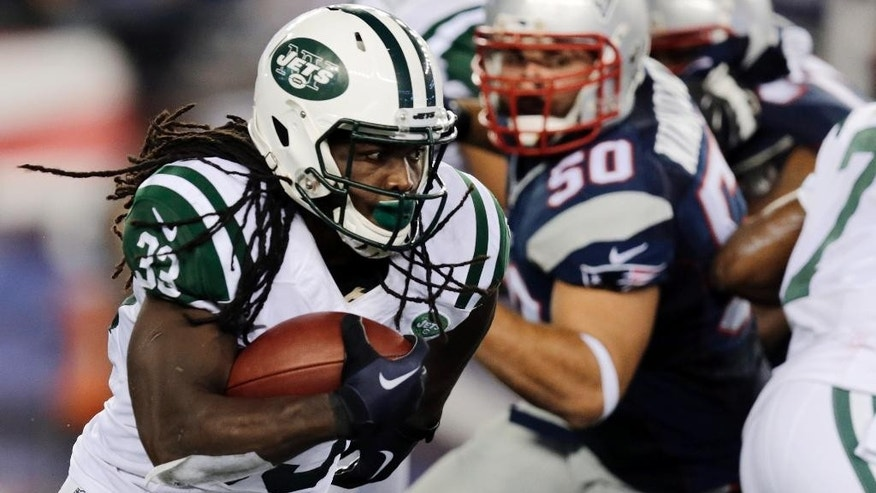 New York Jets running back Chris Ivory (33) runs away from New England Patriots defensive end Rob Ninkovich (50) during the second half of an NFL football game Thursday, Oct. 16, 2014, in Foxborough, Mass. (AP Photo/Charles Krupa)