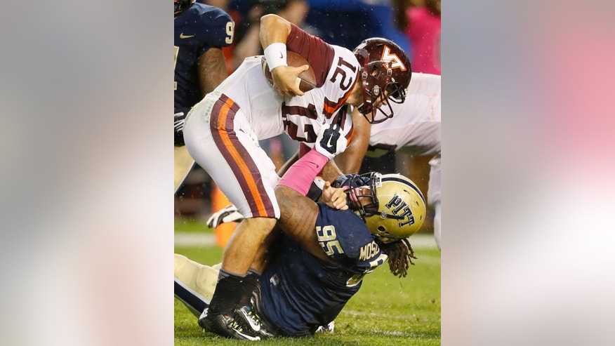 Pittsburgh defensive lineman Khaynin Mosley-Smith (95) sacks Virginia Tech quarterback Michael Brewer (12) during the fourth quarter of an NCAA college football game Thursday, Oct. 16, 2014, in Pittsburgh. Pittsburgh won 21-16. (AP Photo/Keith Srakocic)