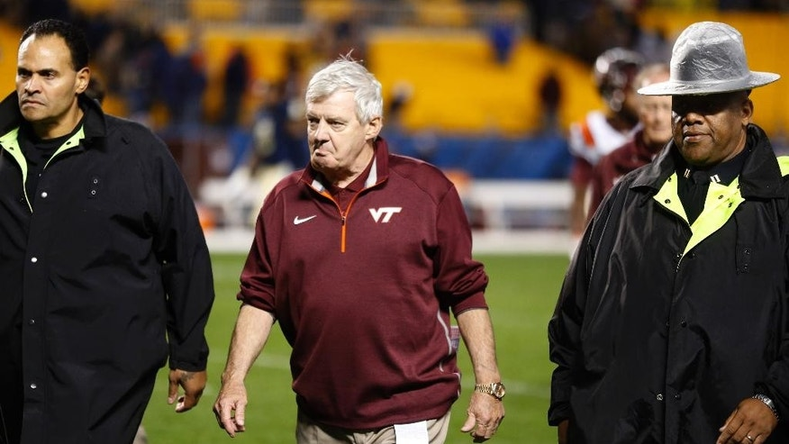 Police escort Virginia Tech head coach Frank Beamer, center, from the field after his team lost to Pittsburgh in an NCAA football game on Thursday, Oct. 16, 2014, in Pittsburgh. Pittsburgh won 21-16. (AP Photo/Keith Srakocic)