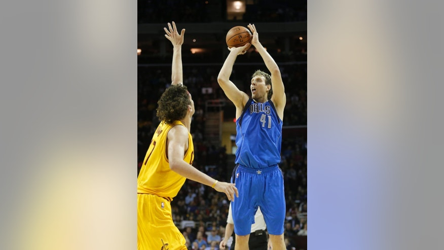 Dallas Mavericks' Dirk Nowitzki (41), from Germany, shoots over Cleveland Cavaliers' Anderson Varejao, from Brazil, during the second quarter of a preseason NBA basketball game Friday, Oct. 17, 2014, in Cleveland. (AP Photo/Mark Duncan)