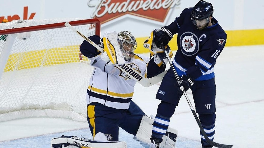 Nashville Predators goaltender Pekka Rinne (35) gets his sleeve on the deflection from Winnipeg Jets' Andrew Ladd (16) during the first period of an NHL hockey game Friday, Oct. 17, 2014, in Winnipeg, Manitoba. (AP Photo/The Canadian Press, John Woods)