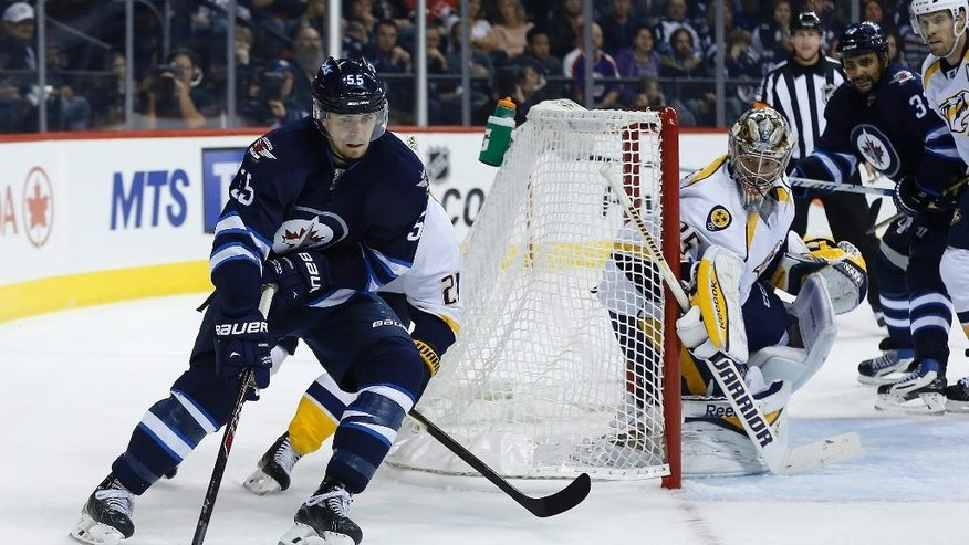 Winnipeg Jets' Mark Scheifele (55) attempts a wraparound against Nashville Predators goaltender Pekka Rinne during the second period of an NHL hockey game Friday, Oct. 17, 2014, in Winnipeg, Manitoba. (AP Photo/The Canadian Press, John Woods)