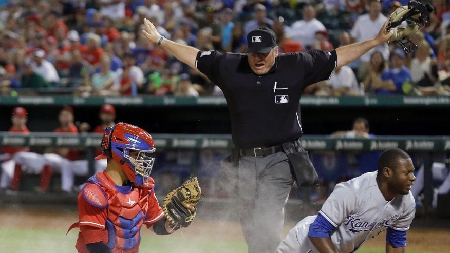 FILE - In this Aug. 23, 2014, file photo, home plate umpire Hunter Wendelstedt, center, calls Kansas City Royals' Lorenzo Cain, right, safe at home after Cain scored against Texas Rangers catcher Robinson Chirinos during a baseball game in Arlington, Texas. A person familiar with the decision tells The Associated Press that the seven-man umpire crew for the World Series will include a rare four first-timers, one of them Wendelstedt. (AP Photo/LM Otero, File)