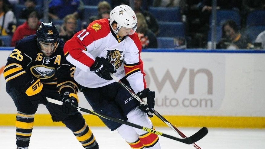 Buffalo Sabres left winger Matt Moulson (26) stick-checks Florida Panthers left winger Jonathan Huberdeau (11) who carries the puck upice during the first period of an NHL hockey game Friday, Oct., 17, 2014, in Buffalo, N.Y. (AP Photo/Gary Wiepert)