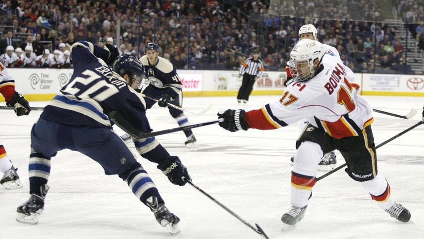 Columbus Blue Jackets' Tim Erixon (20) blocks a shot by Calgary Flames' Lance Bouma (17) during the first period of an NHL hockey game, Friday, Oct. 17, 2014, in Columbus, Ohio. (AP Photo/ Mike Munden)