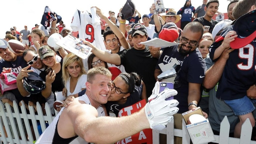 FILE - In this July 26, 2014, file photo, Houston Texans defensive end J.J. Watt, left, takes a selfie with Nina Munduia after an NFL football training camp practice in Houston. Watt is swatting down passes and scoring touchdowns. And with his squeaky-clean image and down-home demeanor he's a godsend for a league facing intense criticism for the off the field behavior of some of its biggest stars. (AP Photo/David J. Phillip, File)