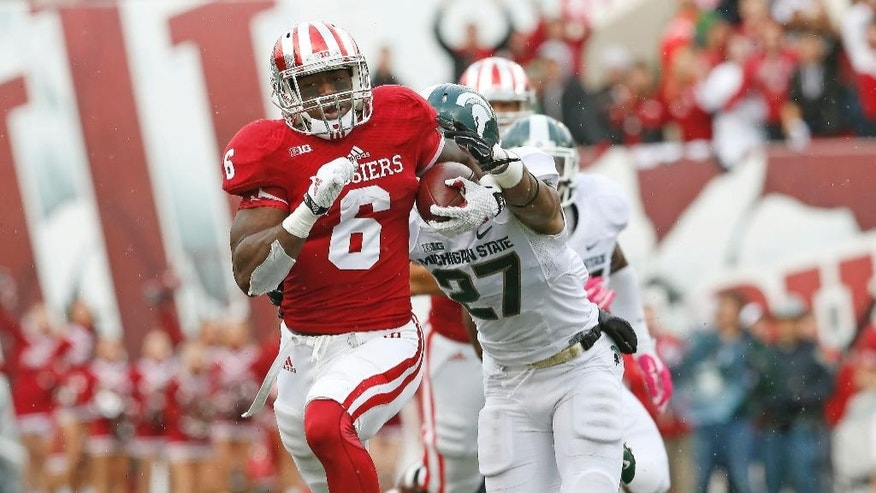 Indiana running back Tevin Coleman (6) tries to escape Michigan State safety Kurtis Drummond (27) in the first half of an NCAA college football game in Bloomington, Ind., Saturday, Oct. 18, 2014. (AP Photo/Sam Riche)