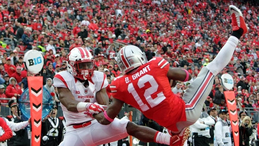 Ohio State cornerback Doran Grant (12) intercepts a pass intended for Rutgers wide receiver Leonte Carroo during the second quarter of an NCAA college football game Saturday, Oct. 18, 2014, in Columbus, Ohio. (AP Photo/Jay LaPrete)