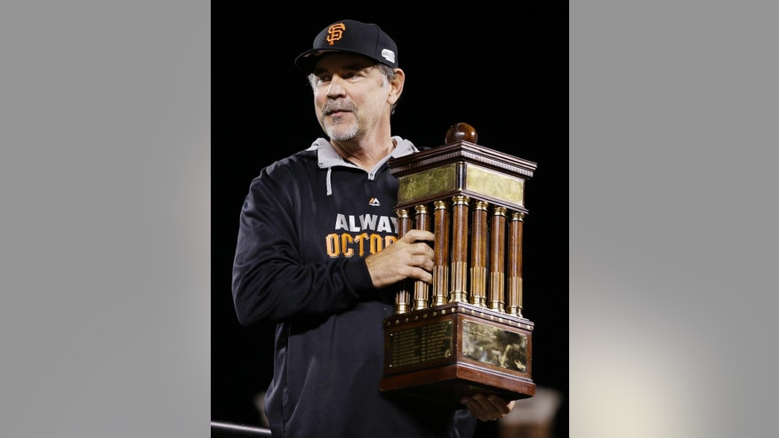 San Francisco Giants manager Bruce Bochy holds the championship trophy after their win against the St. Louis Cardinals in Game 5 of the National League baseball championship series Thursday, Oct. 16, 2014, in San Francisco. (AP Photo/Jeff Roberson)