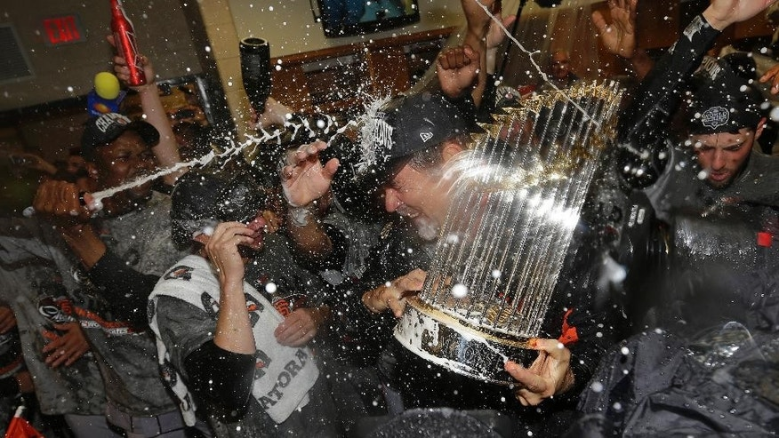 FILE - In this Oct. 29, 2012, file photo, San Francisco Giants manager Bruce Bochy hold the Commissioner's Trophy after Game 4 of baseball's World Series against the Detroit Tigers in Detroit. How do the Giants find a way to win every other October. (AP Photo/David J. Phillip, File)