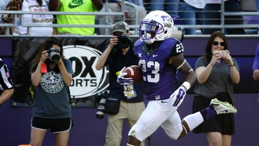 TCU's B.J. Catalon (23) scores on a long run against Oklahoma State in the first half of an NCAA college football game, Saturday, Oct. 18, 2014, in Fort Worth, Texas. (AP Photo/Tony Gutierrez)
