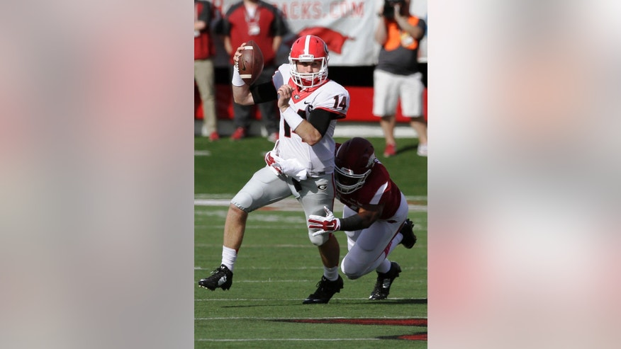 Georgia quarterback Hutson Mason (14) is tackled by Arkansas linebacker Braylon Mitchell in first quarter of an NCAA college football game in Little Rock, Ark., Saturday, Oct. 18, 2014. (AP Photo/Danny Johnston)