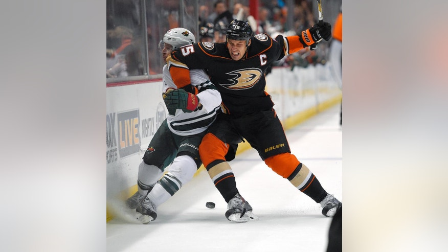 Anaheim Ducks center Ryan Getzlaf, right, puts Minnesota Wild right wing Justin Fontaine into the boards during the first period an NHL hockey game Friday, Oct. 17, 2014, in Anaheim, Calif. (AP Photo/Mark J. Terrill)