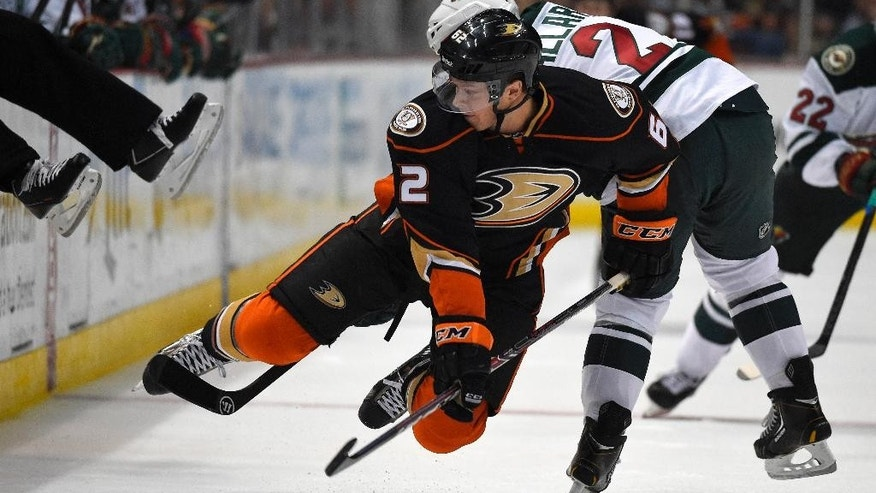 Anaheim Ducks right wing Chris Wagner, left, is tripped by Minnesota Wild defenseman Keith Ballard during the second period an NHL hockey game, Friday, Oct. 17, 2014, in Anaheim, Calif. (AP Photo/Mark J. Terrill)