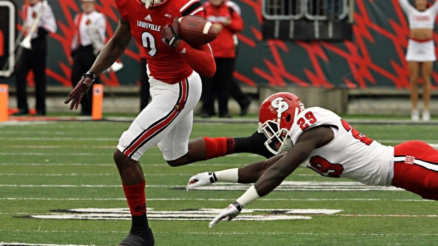 Louisville wide receiver DeVante Parker (9) nearly loses the football trying to get away from North Carolina State's Jack Tocho (29) after making a  reception in the first half of thei  NCAA college football game Saturday, Oct. 18, 2014 in Louisville, Ky. (AP Photo/Garry Jones)