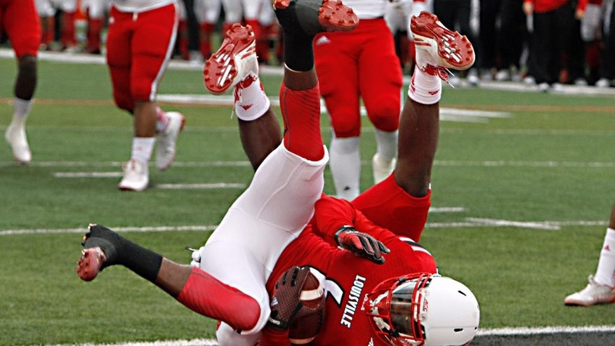 Louisville wide receiver Eli Rogers (6) is pulled diwn in the end zone by  North Carolina State tackler Germaine Pratt  as Rogers catches a touchdown  in the first half of their NCAA college football game Saturday, Oct. 18, 2014 in Louisville, Ky. (AP Photo/Garry Jones)
