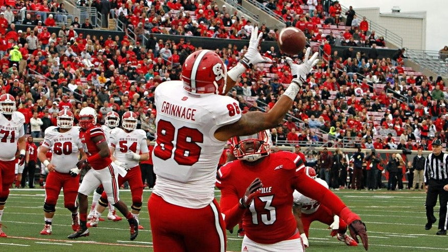 North Carolina State tight end David Grinnage (86) makes a touchdown pass reception over the top of Louisville defender James Burgess (13) in the first half of their NCAA college football game Saturday, Oct. 18, 2014 in Louisville, Ky. (AP Photo/Garry Jones)