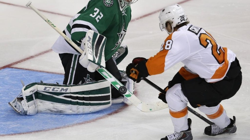 Dallas Stars goalie Kari Lehtonen (32) blocks the puck against Philadelphia Flyers center Claude Giroux (28) during the second period of an NHL hockey game Saturday, Oct. 18, 2014, in Dallas. (AP Photo/LM Otero)