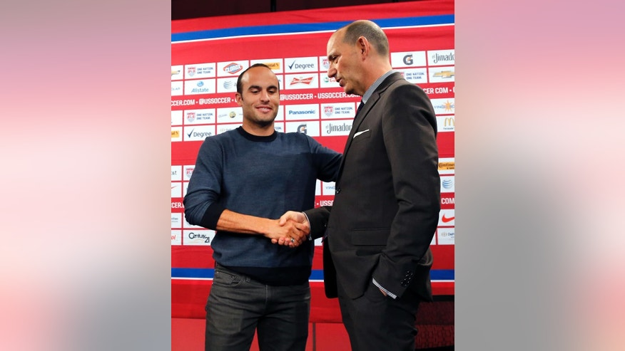 In this Oct. 10, 2014, photo, Major League Soccer Commissioner Don Garber, right, shakes hands with Landon Donovan after a news conference in Bristol, Conn. Garber took the extraordinary step Wednesday, Oct. 15, of criticizing U.S. coach Jurgen Klinsmann for not taking Landon Donovan to the World Cup and for saying Clint Dempsey and Michael Bradley damaged their careers by returning to MLS from European clubs. (AP Photo/Elise Amendola)