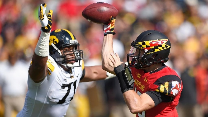 Maryland quarterback C.J. Brown, right, passes as he is pressured by Iowa defensive lineman Carl Davis during the first half of an NCAA college football game, Saturday, Oct. 18, 2014, in College Park, Md. (AP Photo/Nick Wass)