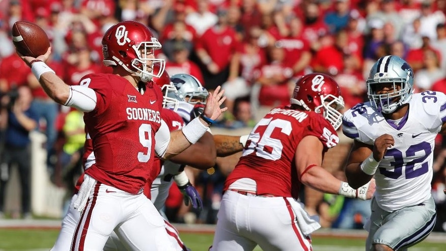 Oklahoma quarterback Trevor Knight (9) passes under pressure from Kansas State linebacker Dakorey Johnson (32) in the first quarter of an NCAA college football game in Norman, Okla., Saturday, Oct. 18, 2014. (AP Photo/Sue Ogrocki)