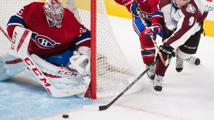 Montreal Canadiens goaltender Carey Price, left, keeps an eye on the play as Canadiens' David Desharnais, center, defends against Colorado Avalanche player Matt Duchene (9) during the first period of an NHL hockey game, Saturday, Oct. 18, 2014  in Montreal. (AP Photo/The Canadian Press, Graham Hughes)