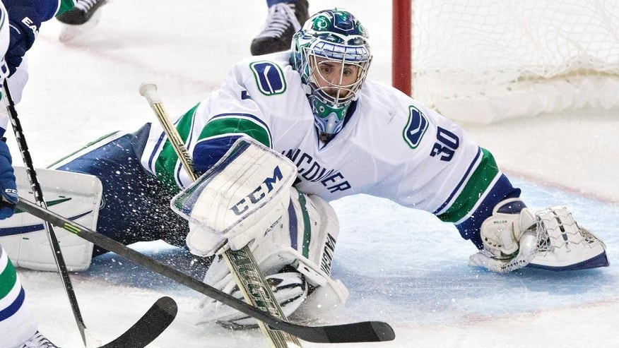 Vancouver Canucks goalie Ryan Miller (30) makes a save against the Edmonton Oilers during the third period of an NHL hockey game Friday, Oct. 17, 2014, in Edmonton, Alberta. The Canucks won 2-0. (AP Photo/The Canadian Press, Jason Franson)