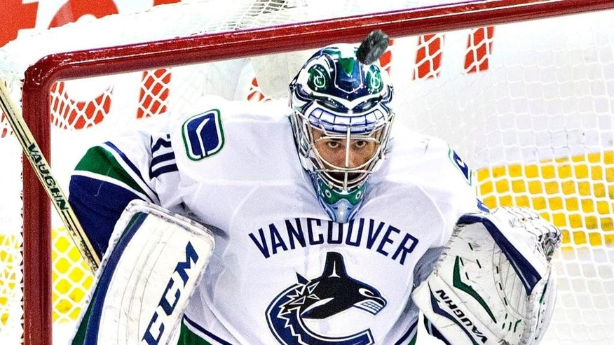 Vancouver Canucks goalie Ryan Miller makes a save on the Edmonton Oilers during the second period of an NHL hockey game Friday, Oct. 17, 2014, in Edmonton, Alberta. (AP Photo/The Canadian Press, Jason Franson)
