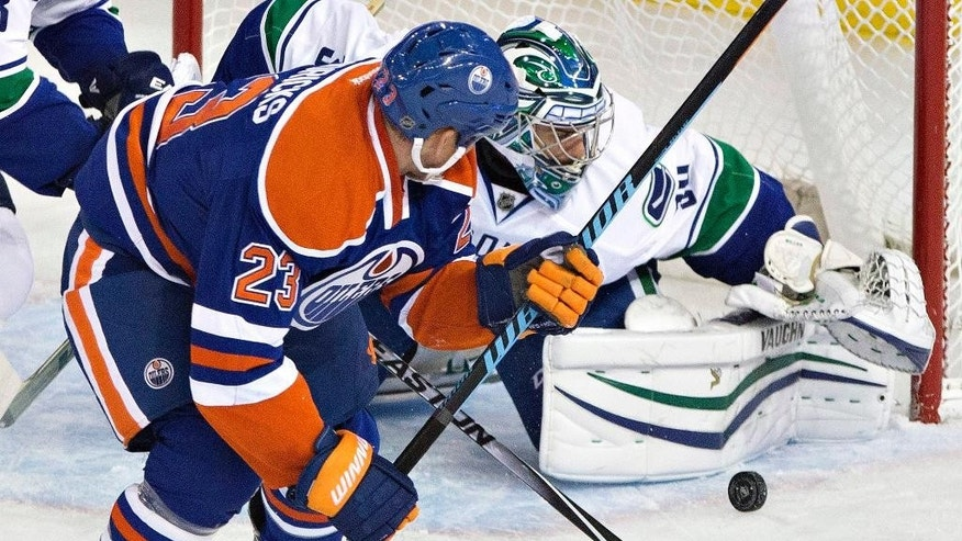 Vancouver Canucks goalie Ryan Miller (30) makes a save on Edmonton Oilers' Matt Hendricks (23) during the second period of an NHL hockey game Friday, Oct. 17, 2014, in Edmonton, Alberta. (AP Photo/The Canadian Press, Jason Franson)