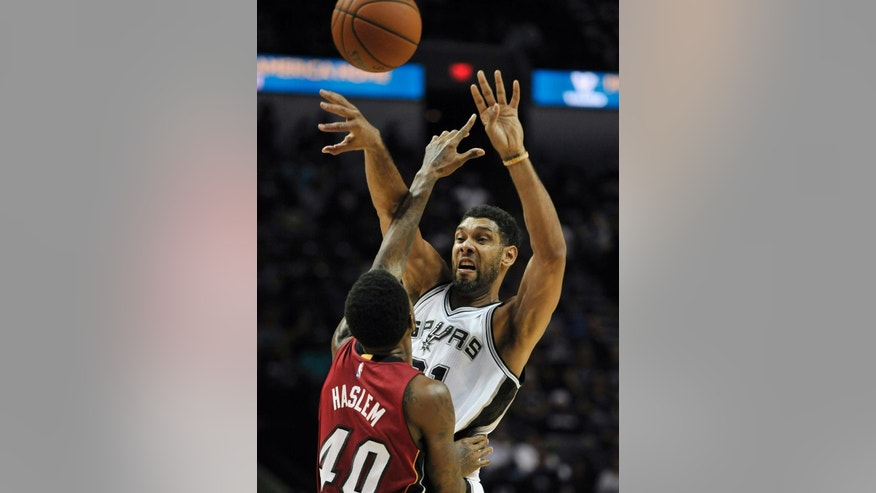 San Antonio Spurs forward Tim Duncan, right, passes the ball over Miami Heat forward Udonis Haslem during the first half of an NBA preseason basketball game, Saturday, Oct. 18, 2014, in San Antonio. (AP Photo/Darren Abate)