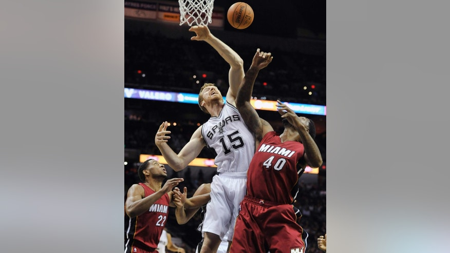 The ball is knocked away from San Antonio Spurs forward Matt Bonner, center, as Miami Heat's Udonis Haslem, right, and Danny Granger defend during the first half of an NBA preseason basketball game, Saturday, Oct. 18, 2014, in San Antonio. (AP Photo/Darren Abate)