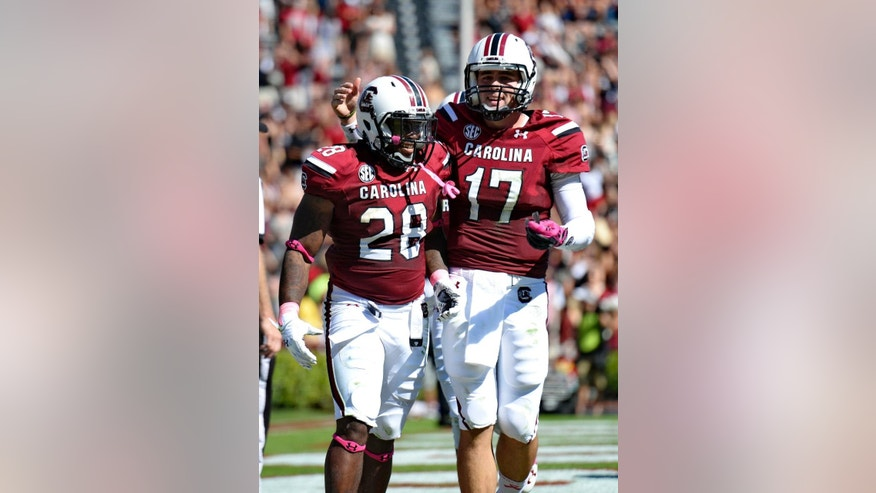 CORRECTS DATE - South Carolina quarterback Dylan Thompson (17) celebrates with Mike Davis after Davis scored his second touchdown on the first half of an NCAA college football game against Furman in Columbia, S.C.,  Saturday, Oct. 18, 2014. (AP Photo/ Richard Shiro)