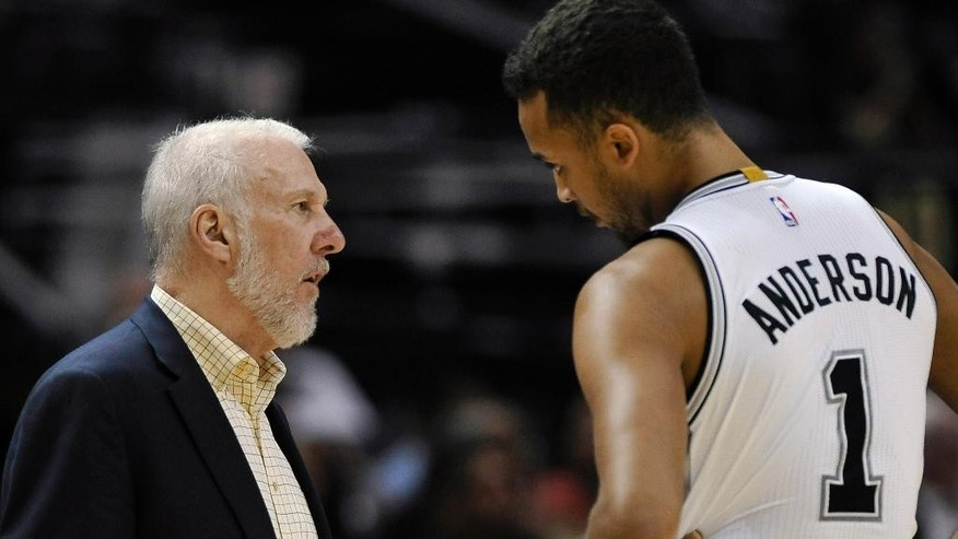 San Antonio Spurs coach Gregg Popovich, left, talks with  forward Kyle Anderson during the second half of a preseason NBA basketball game against the Miami Heat, Saturday, Oct. 18, 2014, in San Antonio. (AP Photo/Darren Abate)