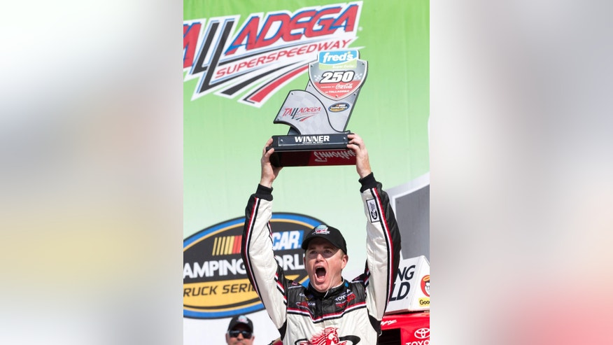 Driver Timothy Peters holds up the trophy in Victory Lane after winning the NASCAR Truck series auto race at Talladega Superspeedway Saturday, Oct. 18, 2014, in Talladega, Ala.   (AP Photo/John Bazemore)