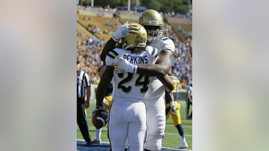 UCLA running back Paul Perkins, left, is greeted by teammate Caleb Benenoch, right, after scoring a touchdown during the first half of a NCAA college football game against California, Saturday, Oct. 18, 2014, in Berkeley, Calif. (AP Photo/Eric Risberg)