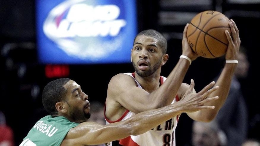 Maccabi Haifa forward Rene Rougeau, left, plays tight defense on Portland Trail Blazers forward Nicolas Batum, from France, during the first half of an NBA exhibition basketball game in Portland, Ore., Friday, Oct. 17, 2014. (AP Photo/Don Ryan)