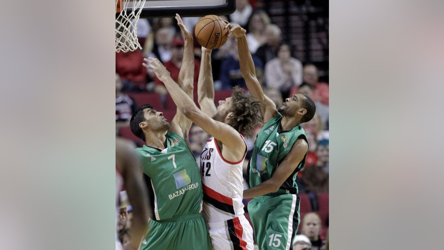 Portland Trail Blazers center Robin Lopez, center, tries to shoot against defense from Maccabi Haifa's Rene Rougeau, right, and Alex Chubrevich during the first half of an NBA exhibition basketball game in Portland, Ore., Friday, Oct. 17, 2014. (AP Photo/Don Ryan)