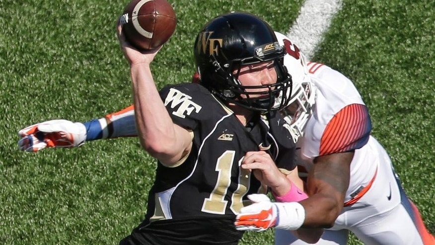 Wake Forest's John Wolford, left, is hit by Syracuse's Dyshawn Davis, right, during the first half of an NCAA college football game in Winston-Salem, N.C., Saturday, Oct. 18, 2014. Wolford left the game after the play. (AP Photo/Chuck Burton)