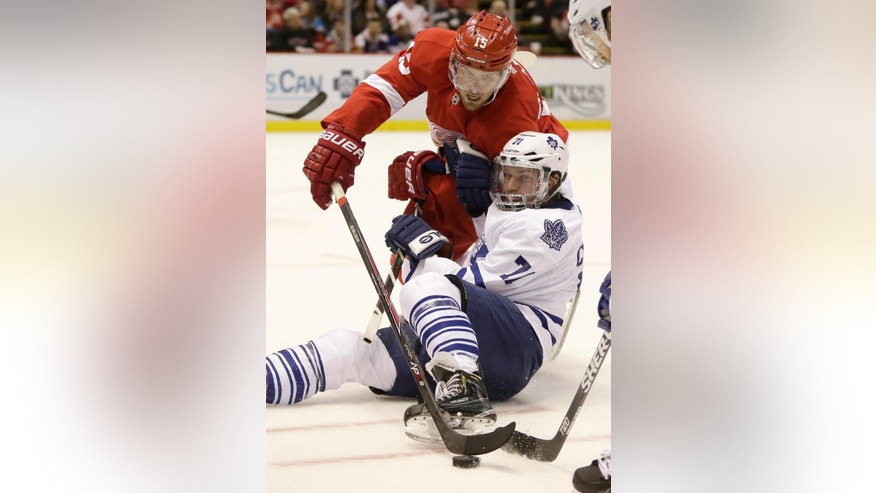 Detroit Red Wings' Riley Sheahan (15) knocks the puck away from Toronto Maple Leafs' David Clarkson during the second period of an NHL hockey games Saturday, Oct. 18, 2014, in Detroit. (AP Photo/Duane Burleson)