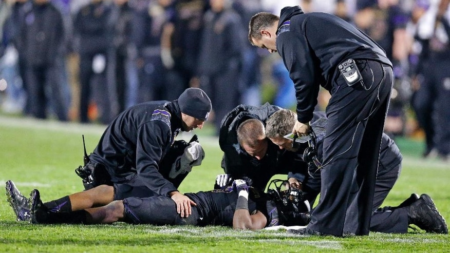 Northwestern wide receiver Miles Shuler is checked by team trainers after aninjury during the second half of an NCAA college football game against Nebraska in Evanston, Ill., Saturday, Oct. 18, 2014. Nebraska won 38-17. (AP Photo/Nam Y. Huh)