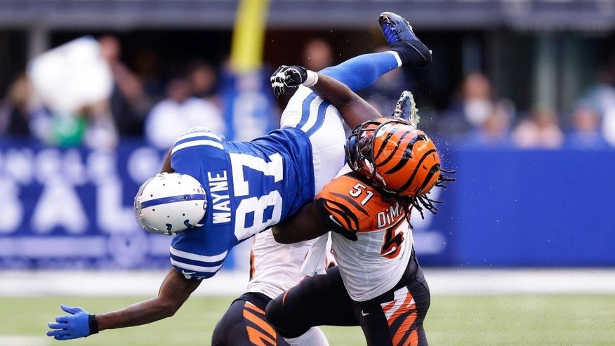 Indianapolis Colts wide receiver Reggie Wayne (87) is tackled by Cincinnati Bengals linebacker Jayson DiManche (51) during the second half of an NFL football game, Sunday, Oct. 19, 2014, in Indianapolis. (AP Photo/Michael Conroy)