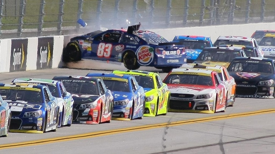 J.J. Yeley (83) wrecks on the backstretch during the NASCAR Sprint Cup Series auto race at Talladega Superspeedway, Sunday, Oct. 19, 2014, in Talladega, Ala. (AP Photo/Greg McWilliams)