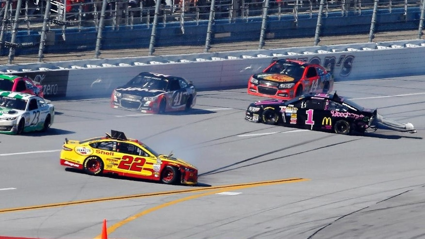 Joey Logano (22) and Jamie McMurray (1) crash as Kurt Busch (41) and Tony Stewart (14) pass by during the NASCAR Sprint Cup Series auto race at Talladega Superspeedway, Sunday, Oct. 19, 2014, in Talladega, Ala. (AP Photo/Butch Dill)