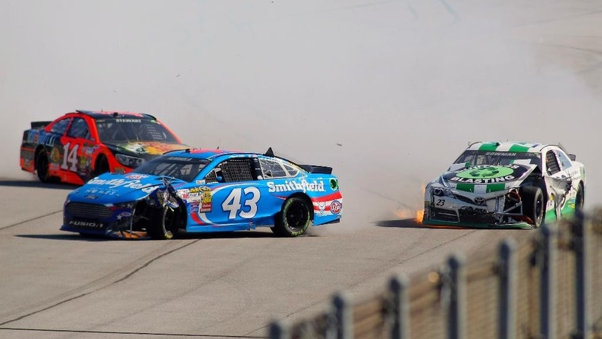 Alex Bowman, right, wrecks with Tony Stewart (14) and Aric Almirola (43) during the NASCAR Sprint Cup Series auto race at Talladega Superspeedway, Sunday, Oct. 19, 2014, in Talladega, Ala. (AP Photo/Greg McWilliams)
