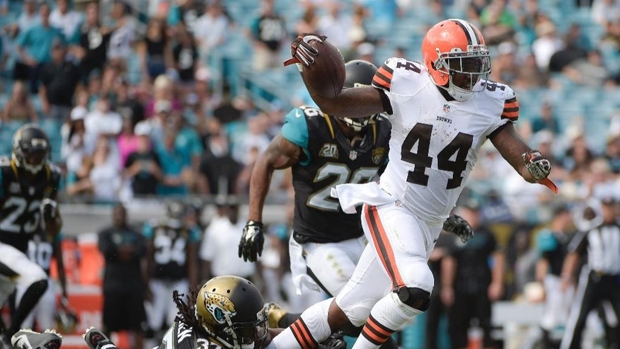 Cleveland Browns running back Ben Tate (44) is tripped up by Jacksonville Jaguars strong safety Johnathan Cyprien (37) during the second half of an NFL football game in Jacksonville, Fla., Sunday, Oct. 19, 2014. (AP Photo/Phelan M. Ebenhack)