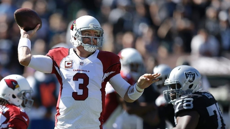 Arizona Cardinals quarterback Carson Palmer (3) passes against the Oakland Raiders during the first quarter of an NFL football game in Oakland, Calif., Sunday, Oct. 19, 2014. (AP Photo/Ben Margot)