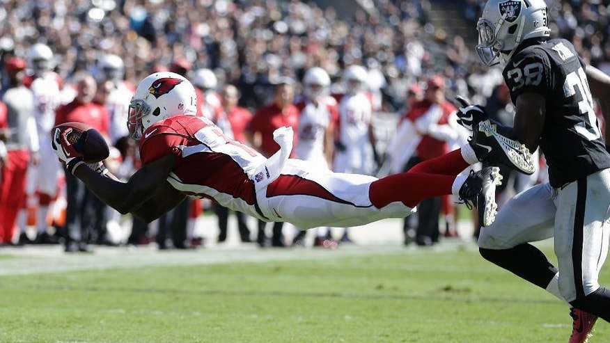 Arizona Cardinals wide receiver Jaron Brown catches a pass in front of Oakland Raiders cornerback T.J. Carrie (38) during the first quarter of an NFL football game in Oakland, Calif., Sunday, Oct. 19, 2014. (AP Photo/Ben Margot)